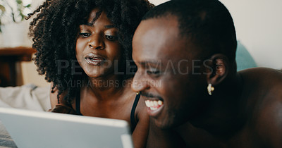 Buy stock photo Shot of a young couple using a digital tablet together in bed at home