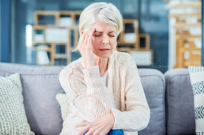 Buy stock photo Shot of a senior woman suffering from a headache while sitting on the sofa at home