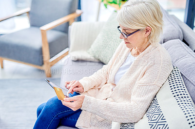 Buy stock photo Shot of a senior woman using a digital tablet and credit card on the sofa at home