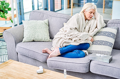 Buy stock photo Shot of a senior woman feeling ill on the sofa at home