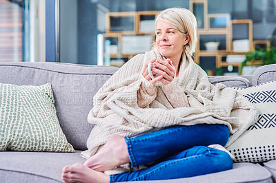Buy stock photo Shot of a senior woman having a relaxing coffee break on the sofa at home