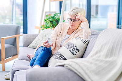 Buy stock photo Shot of a senior woman reading the label on a medicine container at home