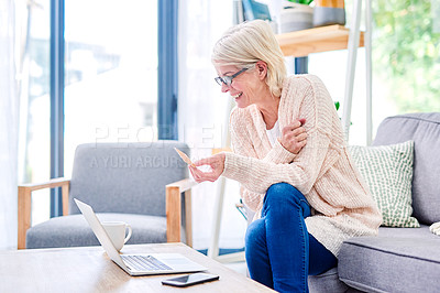 Buy stock photo Shot of a senior woman using a laptop and credit card on the sofa at home