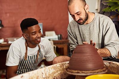 Buy stock photo Shot of two young men working with clay in a pottery studio