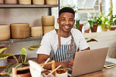 Buy stock photo Shot of a young man using a laptop while working in a ceramic studio