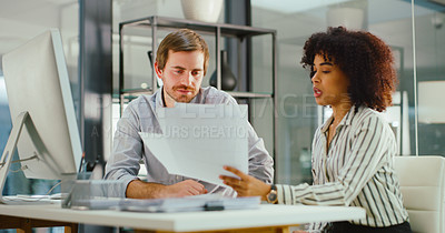 Buy stock photo Shot of a young businessman and businesswoman using a computer and processing paperwork in a modern office