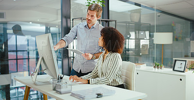 Buy stock photo Shot of a young businessman and businesswoman using a computer and digital tablet in a modern office