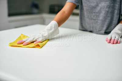 Buy stock photo Closeup shot of an unrecognisable woman wiping a kitchen counter at home