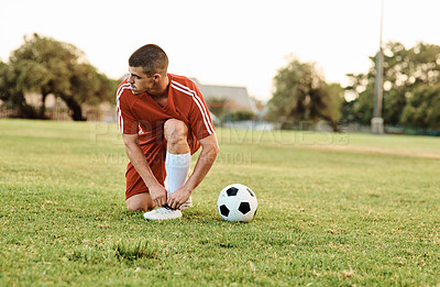 Buy stock photo Shot of a player tying his shoelaces while out on the field