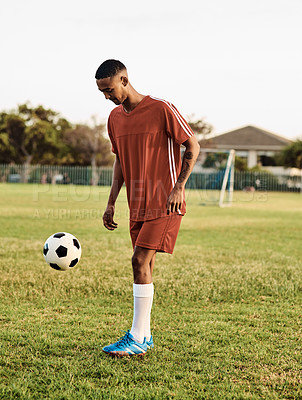 Buy stock photo Shot of a young player out on the field with a soccer ball