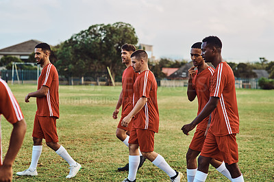 Buy stock photo Shot of a team of soccer players walking together on a sports field