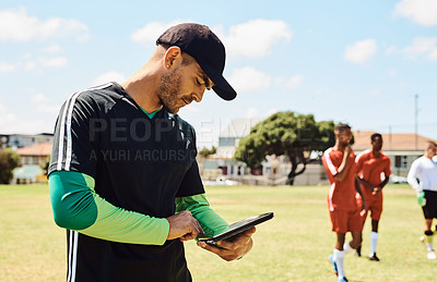 Buy stock photo Shot of a soccer coach using a digital tablet while out on the field