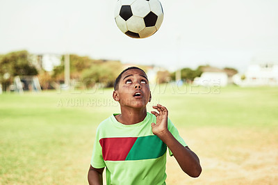 Buy stock photo Shot of a young boy playing soccer on a sports field