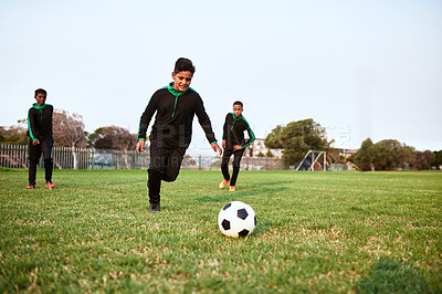 Buy stock photo Shot of a group of young boys playing soccer on a sports field