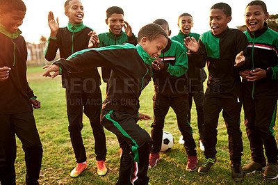 Buy stock photo Shot of a boys soccer team cheering their teammate on a sports field