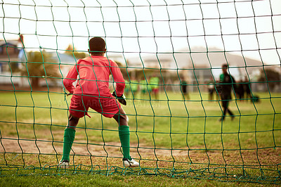 Buy stock photo Rearview shot of a young boy standing as the goalkeeper while playing soccer on a sports field