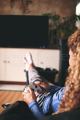 Buy stock photo Cropped shot of an unrecognisable woman playing video games on the sofa at home