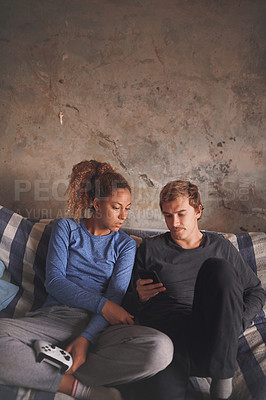 Buy stock photo Shot of a young couple using a smartphone while playing video games on the sofa at home