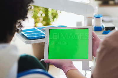 Buy stock photo Shot of a dentist using a digital tablet with a green screen during a consultation with her patient
