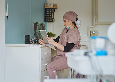 Buy stock photo Shot of a young woman using a digital tablet while working in a dentist's office