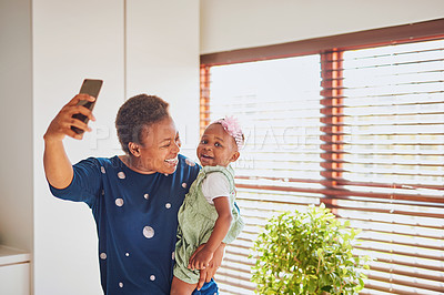 Buy stock photo Shot of an adorable little girl taking selfies with her mother