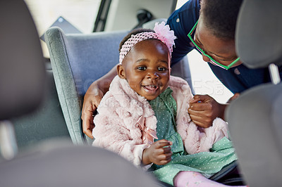 Buy stock photo Shot of an adorable little girl being secured with a safety belt by her mother in a car