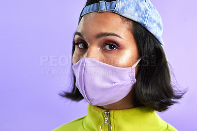 Buy stock photo Studio shot of a beautiful young woman wearing a face mask against a purple background