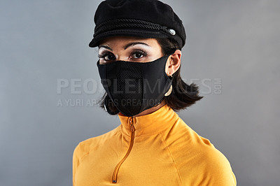 Buy stock photo Studio shot of a beautiful young woman wearing a face mask against a grey background