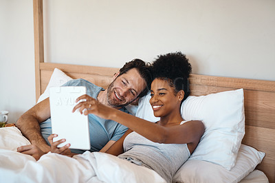 Buy stock photo Shot of a couple using a digital tablet while lying in bed together