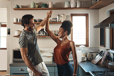 Buy stock photo Cropped shot of an affectionate young couple dancing together in their kitchen at home