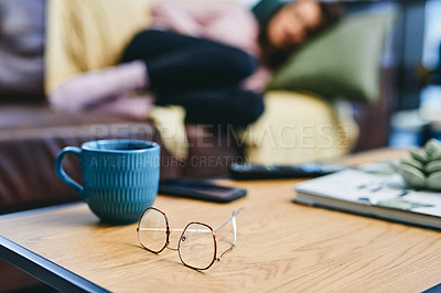 Buy stock photo Shot of reading glasses and a cup on a coffee table at home