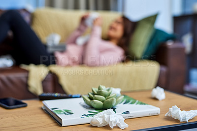 Buy stock photo Shot of a woman using tissues while lying sick at home