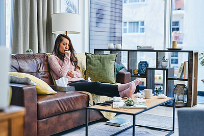 Buy stock photo Shot of a young woman couching while sitting on the couch at home