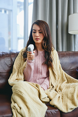 Buy stock photo Shot of a young woman checking her temperature while sitting on the couch at home
