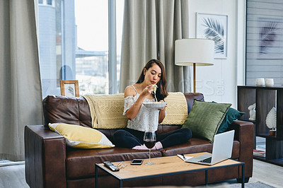 Buy stock photo Shot of a woman sitting at home with food and wine while watching something on her laptop