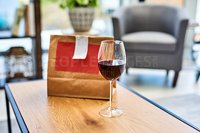 Buy stock photo Shot of a glass of red wine and a takeout paper bag on a table at home