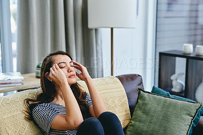 Buy stock photo Shot of a young woman looking stressed while sitting at home