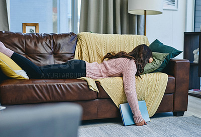 Buy stock photo Shot of a woman falling asleep on the couch with a book in her hand