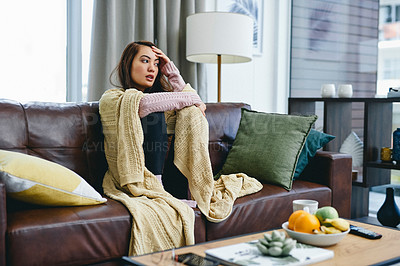 Buy stock photo Shot of a young woman sitting at home with a blanket around her
