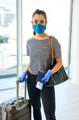 Buy stock photo Shot of a masked young woman carrying her passport and ticket in an airport