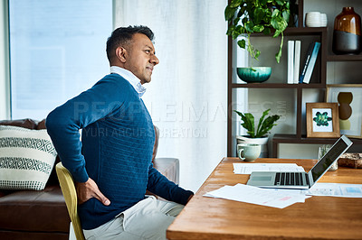 Buy stock photo Shot of a businessman suffering from back pain while working at home