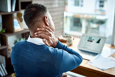 Buy stock photo Shot of a businessman suffering from neck pain while working at home