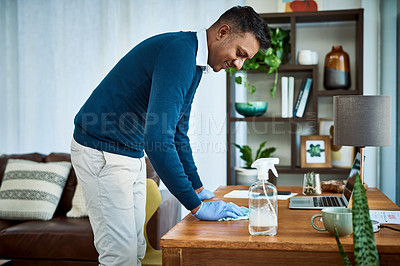 Buy stock photo Shot of a businessman disinfecting his desk while working from home