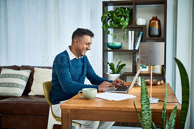 Buy stock photo Shot of a businessman using a laptop while working from home