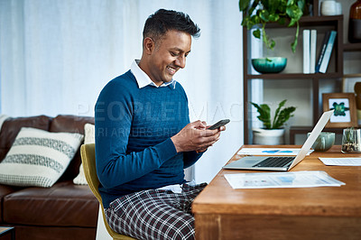 Buy stock photo Shot of a businessman using a laptop and smartphone while working from home