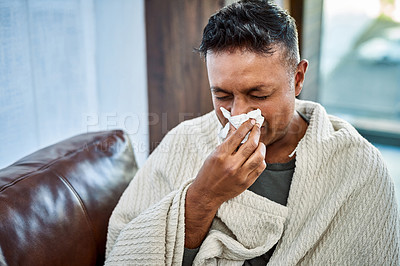 Buy stock photo Shot of a man blowing his nose while recovering from an illness on the sofa at home