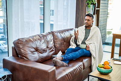 Buy stock photo Shot of a man checking his temperature while recovering from an illness on the sofa at home