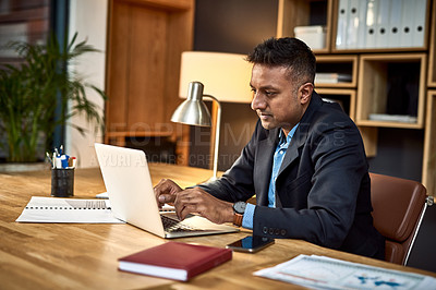 Buy stock photo Shot of a confident businessman using a laptop in a modern office