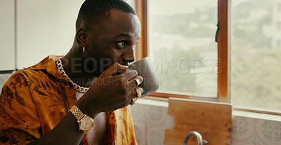 Buy stock photo Shot of a young man enjoying a relaxing coffee break in the kitchen at home
