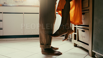 Buy stock photo Shot of an unrecognisable couple sharing a romantic moment in the kitchen